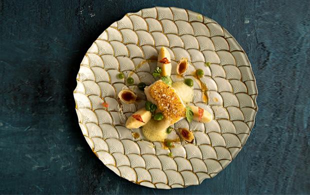 O bacalhau confitado em azeite recebe crosta de chouriço português e é servido com sua brandade nos restaurantes Eleven no Rio de Janeiro e em Lisboa