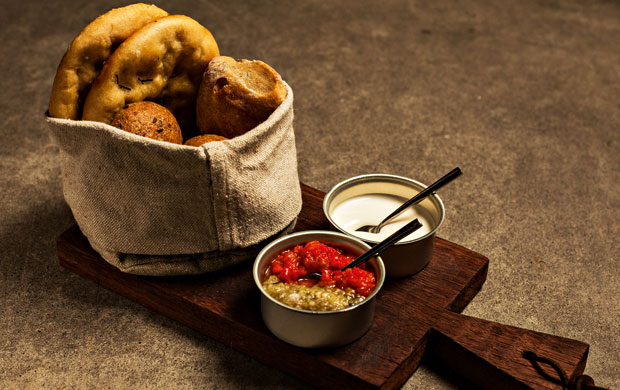 O couvert com pães, maionese de alho e pimentão com berinjela. A